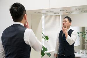 男性が鏡に向かってヒゲを触る様子